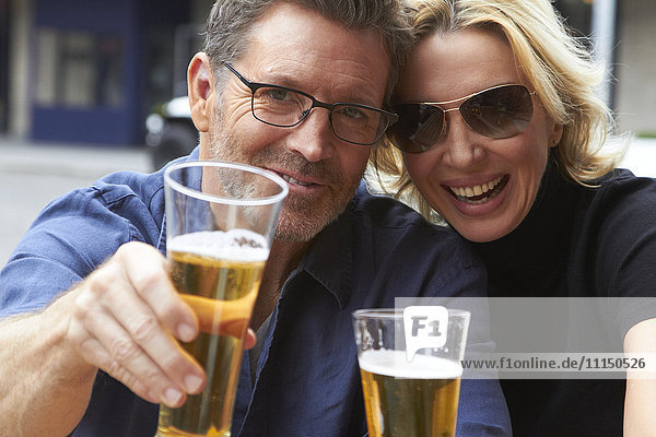 Caucasian couple drinking beer outdoors