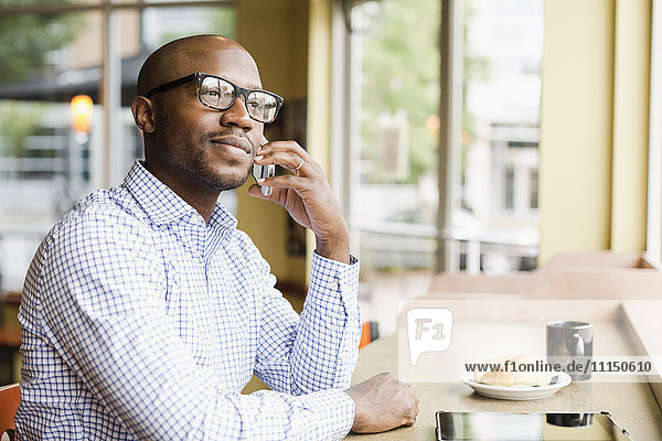 Black man talking on cell phone in coffee shop