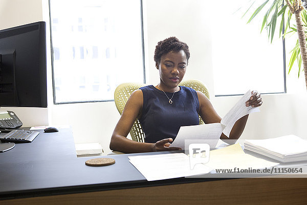 African American businesswoman reading at desk