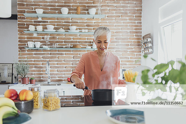 Older Caucasian woman cooking spaghetti in kitchen