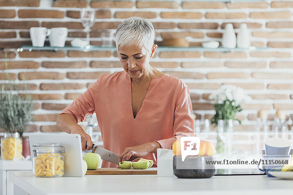 Older Caucasian woman cutting apples in kitchen
