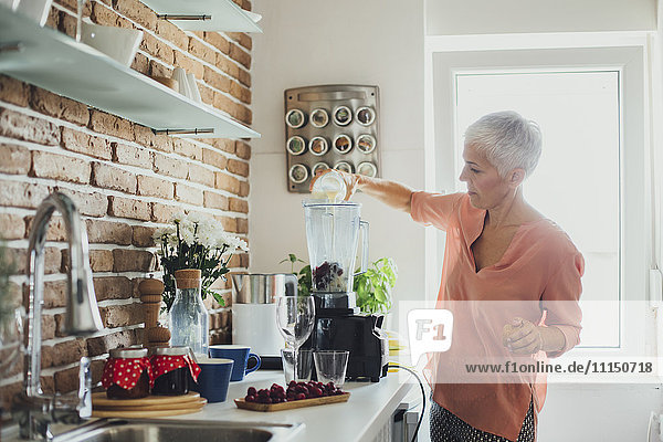 Older Caucasian woman making smoothie in kitchen
