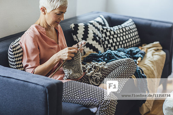 Older Caucasian woman knitting on sofa