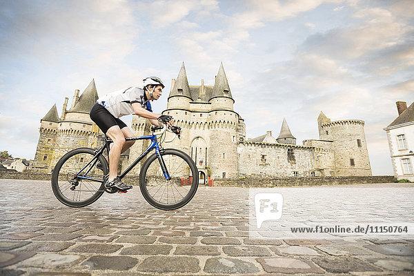 Caucasian man cycling near castle