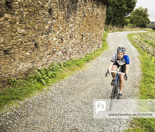 Caucasian man cycling on gravel path