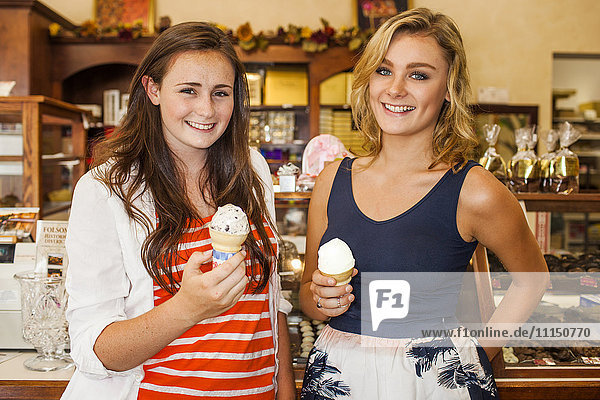 Caucasian teenage girls eating ice cream in candy shop