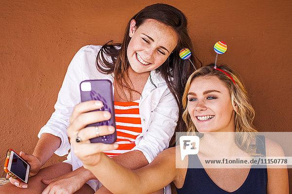 Caucasian teenage girls taking cell phone selfie