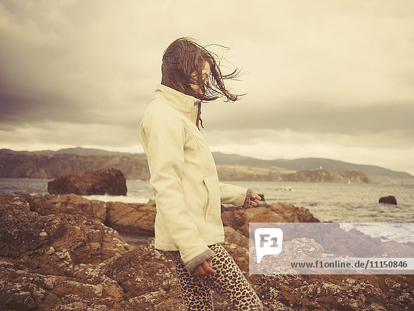 Mixed race girl walking on rocky beach