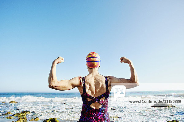 Older Caucasian woman flexing her muscles on beach