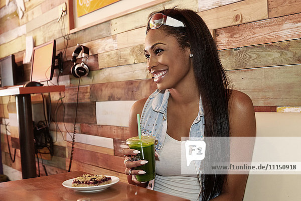 African American woman having juice in cafe