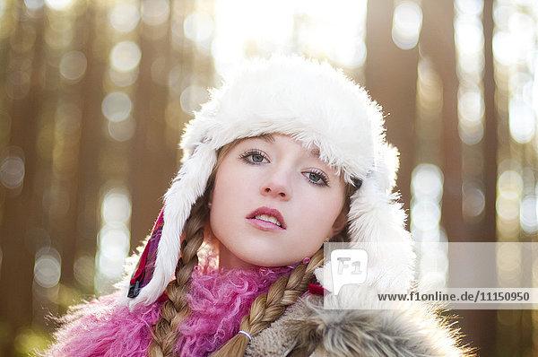 Caucasian teenage girl wearing fuzzy hat outdoors