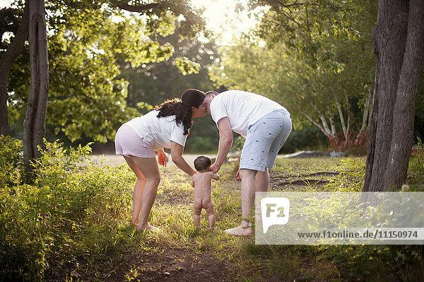 Parents and baby walking in garden