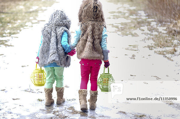 Caucasian girls holding hands in snow