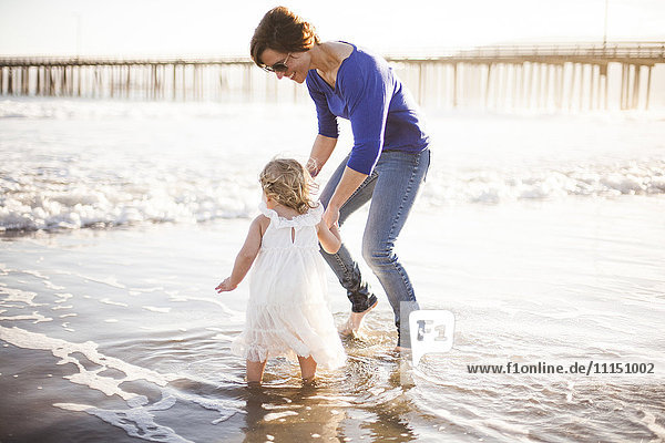 Caucasian mother and daughter walking on beach