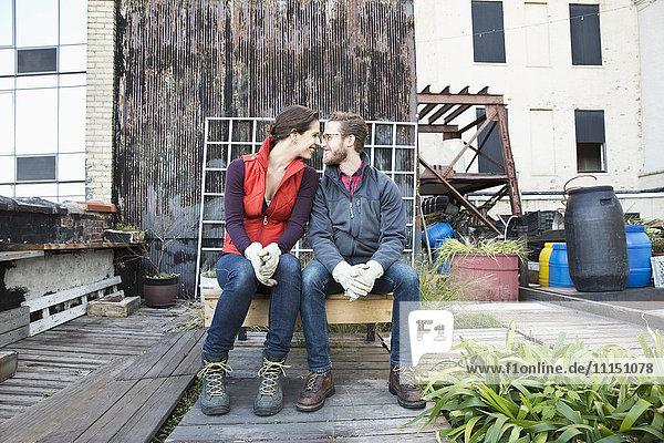 Couple sitting in urban rooftop garden