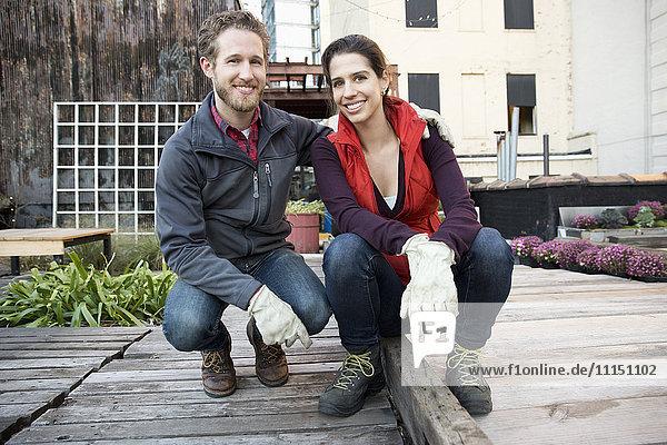 Couple smiling in urban rooftop garden