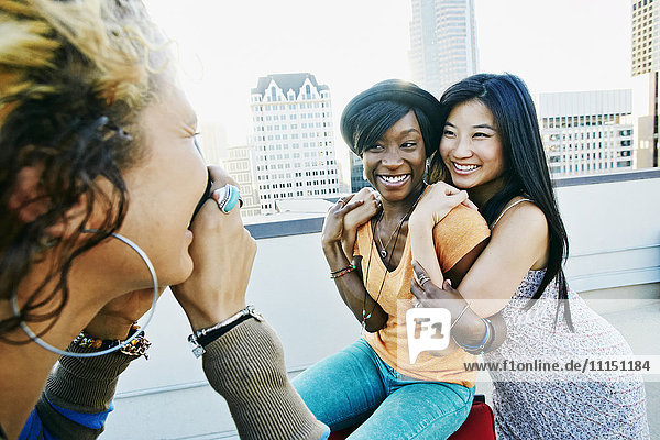 Woman photographing friends on urban rooftop