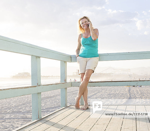 Caucasian woman talking on cell phone on boardwalk at beach