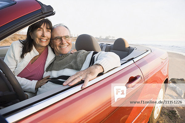 Older couple driving convertible on beach