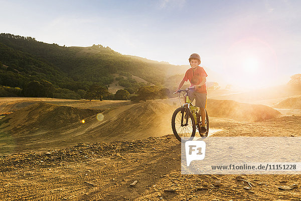 Mixed race boy riding dirt bike on track Mixed race boy riding dirt bike on track