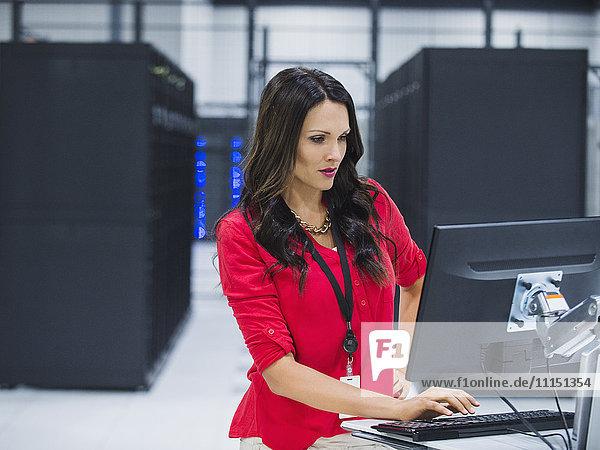 Caucasian businesswoman using computer in server room