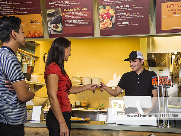 Hispanic woman purchasing food in cafe