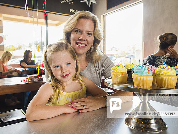 Caucasian mother and daughter smiling in cafe