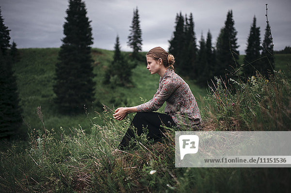 Caucasian woman sitting in remote field