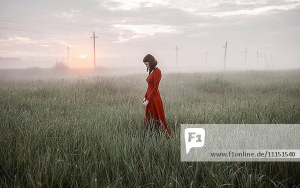 Caucasian woman walking in remote field