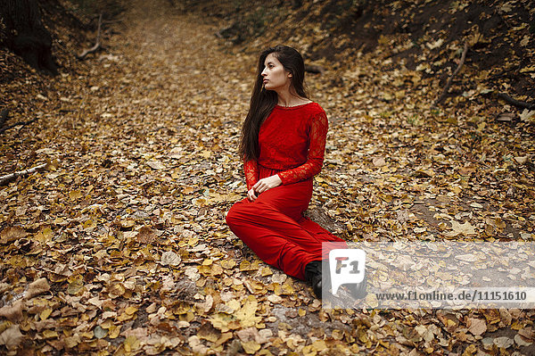 Caucasian woman sitting in autumn leaves