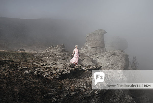 Caucasian woman standing on misty rock formation