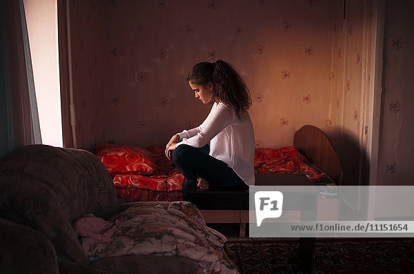 Caucasian woman sitting in bedroom