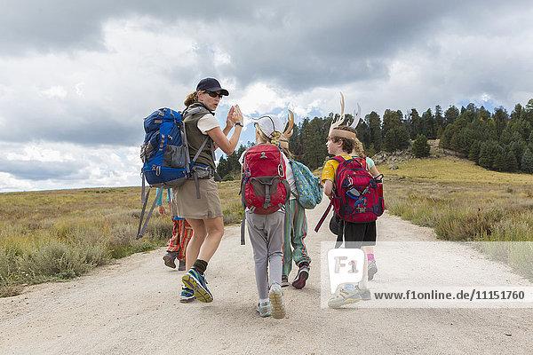 Caucasian hiker leading children on path in remote landscape