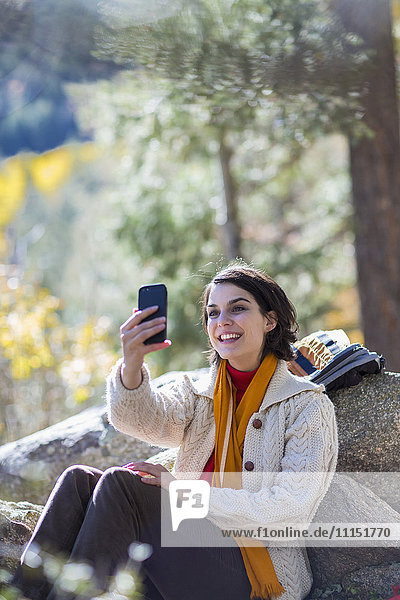 Mixed race hiker taking cell phone selfie in forest