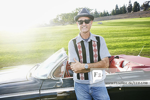 Mixed race man smiling near classic convertible Mixed race man smiling near classic convertible