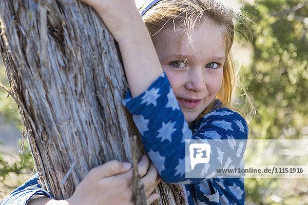 Caucasian girl hugging tree outdoors