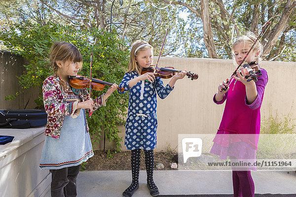 Girls playing violin outdoors