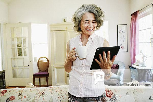 Caucasian woman using digital tablet in living room Caucasian woman using digital tablet in living room
