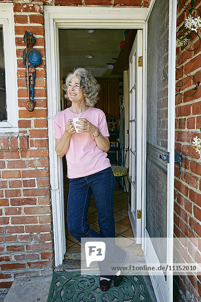 Caucasian woman drinking cup of coffee in doorway