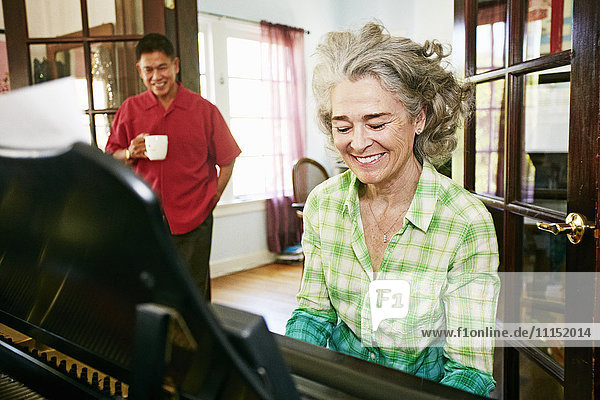 Man watching wife play piano in living room