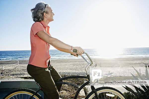 Caucasian woman riding bicycle near beach Caucasian woman riding bicycle near beach