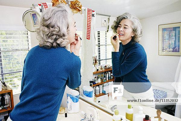 Caucasian woman applying makeup in mirror Caucasian woman applying makeup in mirror