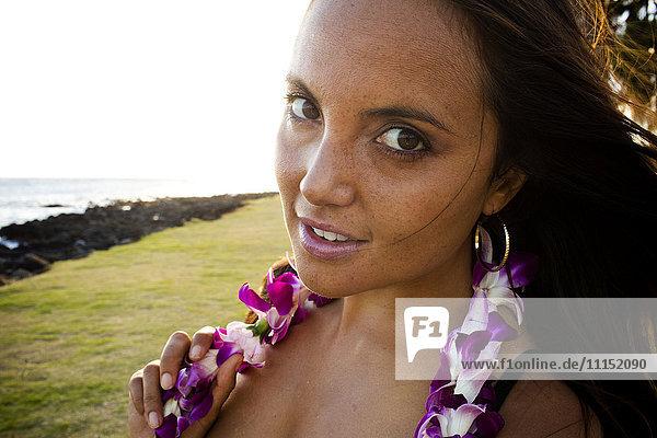 Caucasian woman wearing flower lei near ocean