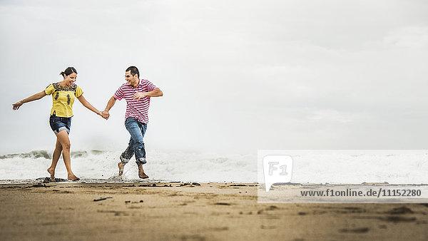 Hispanic couple running in waves on beach