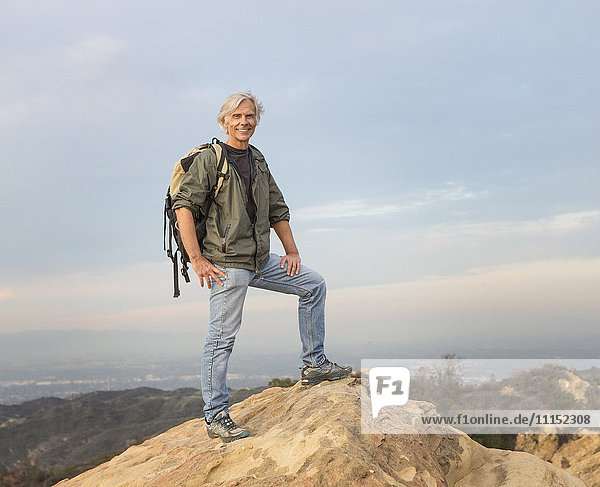 Older Caucasian man standing on rocky hilltop