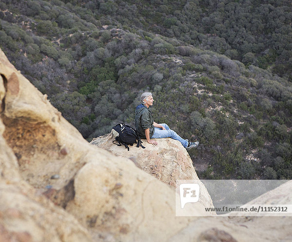 High angle view of older Caucasian man sitting on rock formation