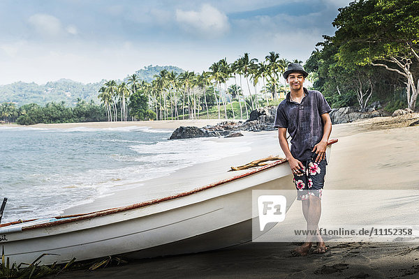 Hispanic man standing near boat on beach