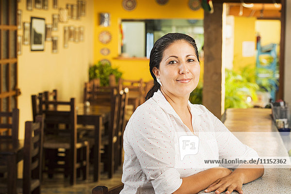 Smiling woman at counter in restaurant