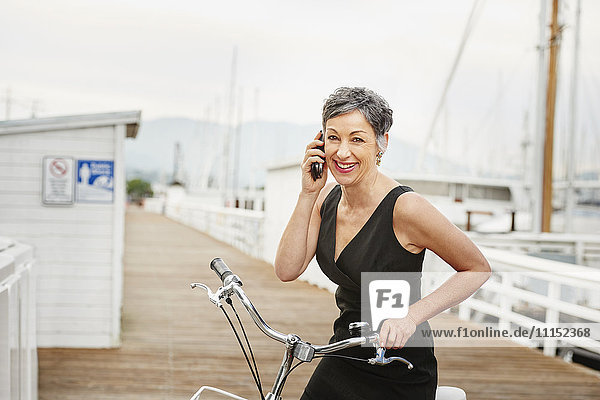 Older Caucasian woman talking on cell phone with bicycle