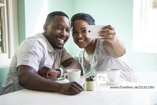Smiling couple taking cell phone selfie at table